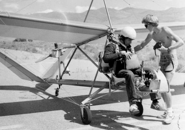 Gil Kensey, hand on parachute, undergoes a flight check as his assistant readies Klaus Hill's second Hummer for take off. Kensey sits astride the forward keel of the taildragger with his helmet at the front of the high wing. A meter directly behind the wing, the small engine and prop are mounted to direct air through the V-tail, Photo by John Coe