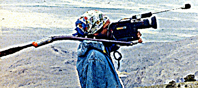 "After suffering a dislocated shoulder in the crash of his Aolus, Rick Masters films ""The Sky Blue Movie""(unreleased) with one arm at Gunter Launch in the White Mountains in July of 1982.  The camera is an Elmo 1012XL S8 loaded with Kodachrome film, one of the most popular professional news cameras of the era, counterbalanced with a weight for smooth panning.  The Gucci scarf was supplied by Bettina Gray."