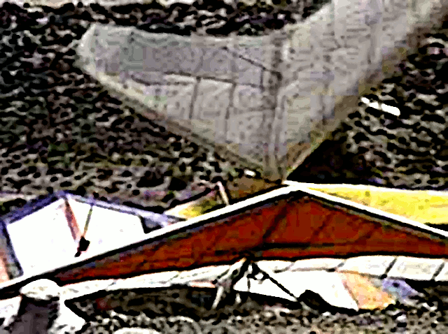 "A frame from ""Aoli, Comet Clones & Pod People"" -  The great dust devil disaster, where a powerful thermal crossed through launch, hurling gliders right and left as pilots struggled to hang on to them.  In this frame, an Owens Valley Racer is hurled above the gliders set up at launch and comes down hard with its nose on the leading edge of another hang glider, breaking it."