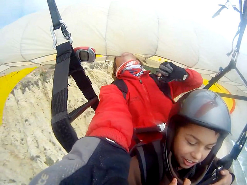 A USHPA commercial  joyrider performs a dangerous stunt by biting the canopy of another paraglider immediately behind him.   He is just above the cliff, flying with a child on the edge of the Paraglider Dead Man's Curve at Torrey Pines in 2015.  The joyrider on the other paraglider is also carrying a child.